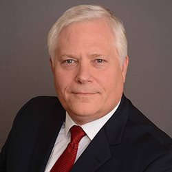 Kurt Alexander headshot image of an older Caucasian man with white hair wearing a black suit, white shirt and red tie.