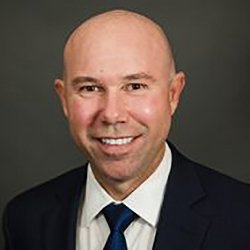 Weston Smith headshot image of a smiling bald Caucasian man wearing a black suit, white shirt, and dark blue tie.
