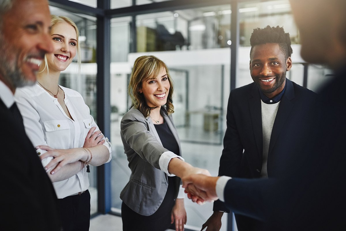 Business professionals in an informal meeting with a man and a woman shaking hands.