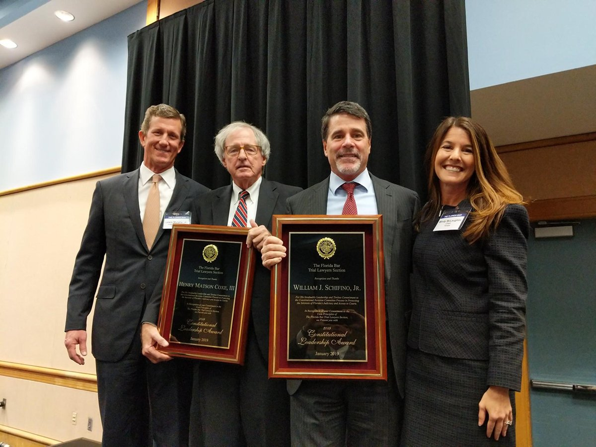 Image of four people getting two award plaques. Three people are Caucasian men and one is a Caucasian woman. There is a black curtain in the background.