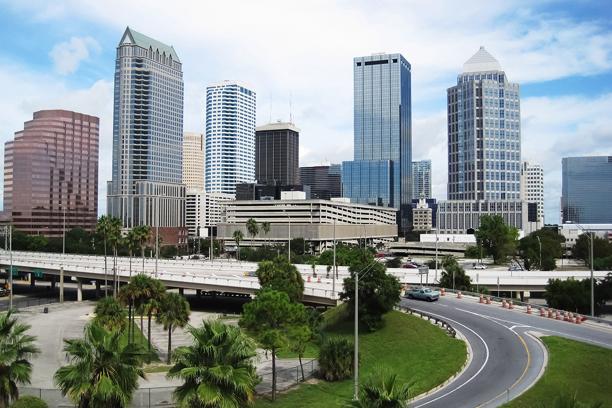 Tampa City Image with tall buildings, a freeway on-ramp, and palm trees.