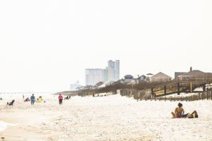 Pensacola Beach image, with people walking on the beach, some homes and hotels off in the distance in the background.