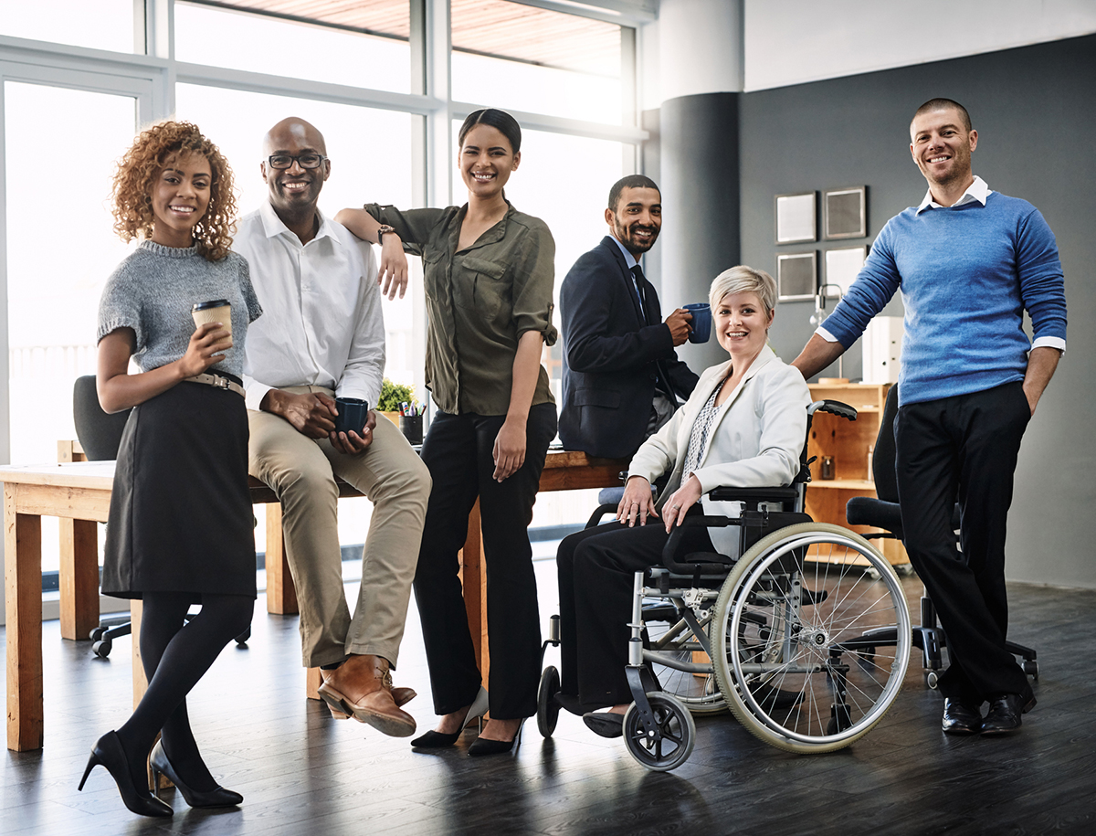 Diverse business people in an office. People of all ages, racial backgrounds, in a wheelchair, etc.standing together in their business attire.